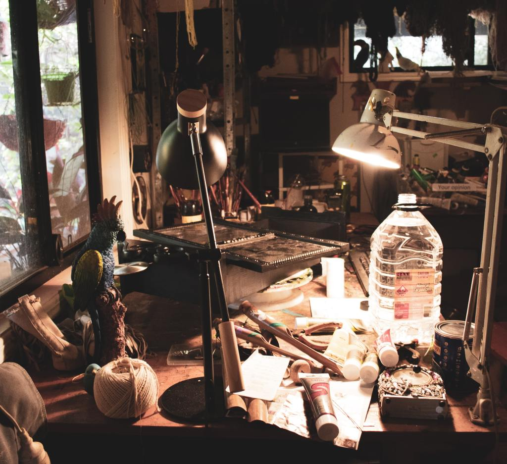 Photo of an art studio in dim light, there is a workbench lit slightly by a few desk lamps. On the table are various art supplies including paint, brushes, string and so on but nothing is the main focus.