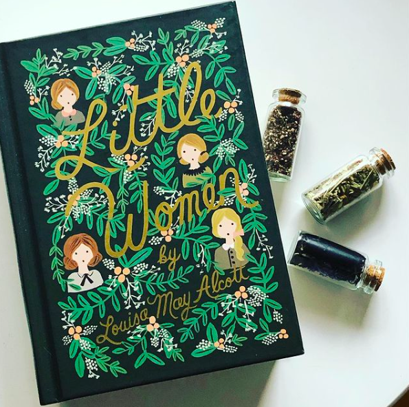 Photo of hardcover Little Women by Louisa May Alcott from the Penguin in Bloom series which features gorgeous illustrations of the March sisters surrounded with bright green leaves. The book rests on a white background, with three small glass vials filled the tea placed on the right side.